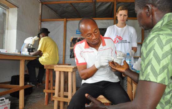 En sygeplejerske fra det mobile hold, tager blod fra fingerspidsen på en af de lokale beboere, for at teste for sovesyge.
