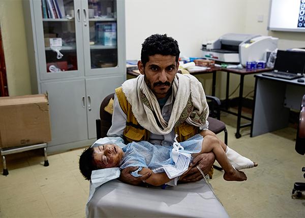 En far holder sit sårede barn på hospitalet vi støtter i Sa'ada. © Sebastiano Tomada/Getty Reportage