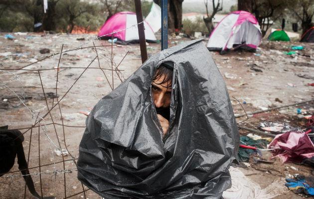 En mand fra Afghanistan forsøger at holde regnen ude med en plasticsæk som eneste værn. © Alessandro Penso