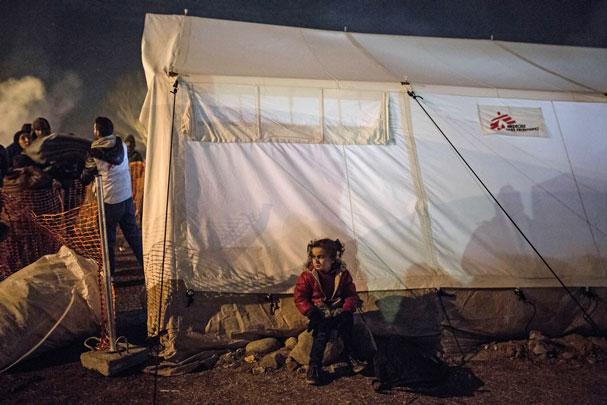 En pige venter på sin mor udenfor Læger uden Grænsers telt, hvor der deles tæpper ud.