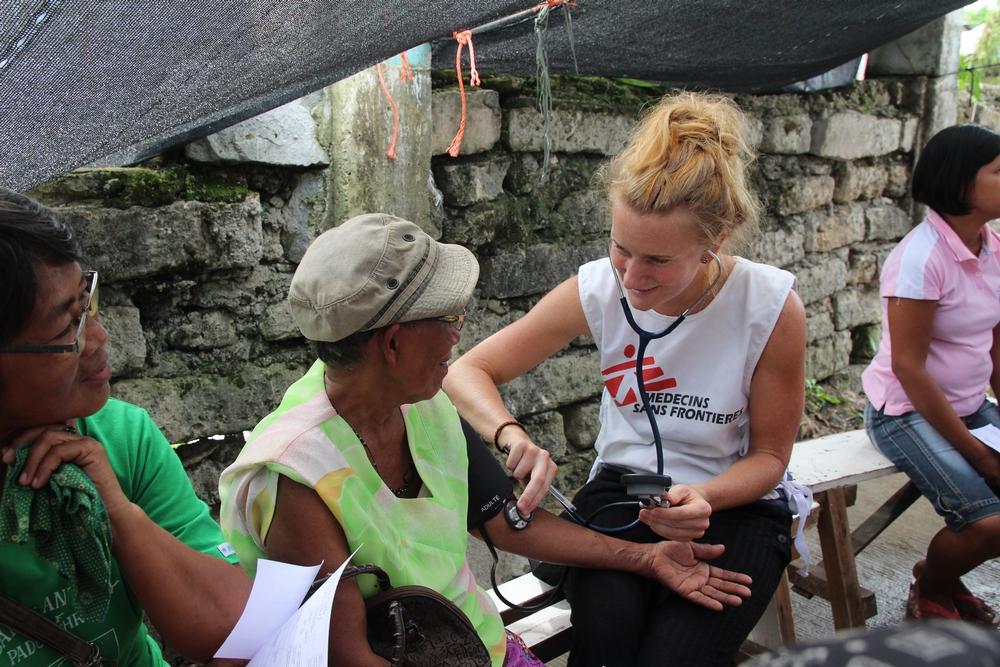 En læge tjekker blodtrykket på en kvinde en måned efter, at en kraftig tyfon har ramt Filippinerne.