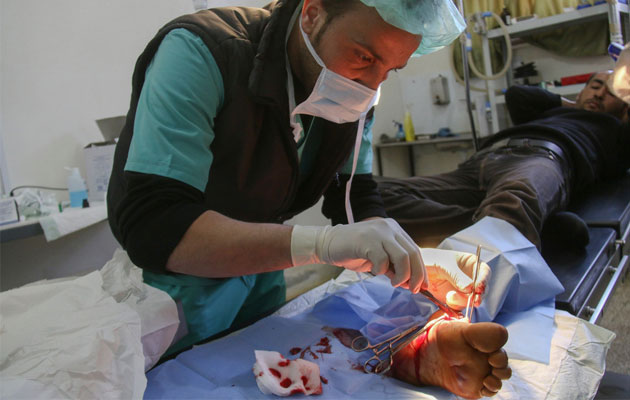 En læge opererer en patient på Læger uden Grænsers Al Salamah-hospital i det nordlige Syrien.