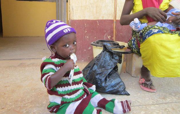 Umma spiser Plumpy Nut og igen rask efter malariaen. Moderen og lillesøsteren har det også godt - de sidder i baggrunden.