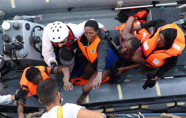 Rædselsslagne flygtninge bliver hjulpet ombord på Læger uden Grænsers redningsskib efter en redningsaktion.