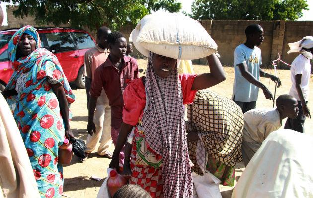 Maira Modus familie var en ud af 500 familier, der modtog mad. På hovedet bærer hun en sæk med 25 kilo hirse, mens hun bærer sit yngste yngste barn på et år på ryggen.
