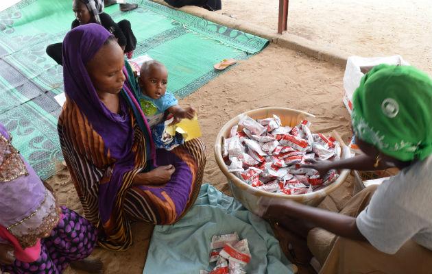 """Her er et eksempel på udlevering af Plumpy Nut. Amaboua Ab besøger en af vores klinikker i Chad. Hendes barn er seks en halv måned gammel og lider af underernæring. Hun får udleveret """"Plumpy Nut"""" til en uges brug. Så vender hun tilbage til klinikken og får undersøgt sit barns tilstand, og om barnet stadig har brug for den næringsberigede mad. © Charlotte Morris"""