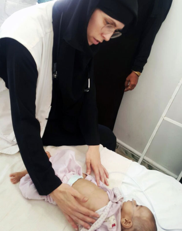 Astrid undersøger et underernæret barn på hospitalet.