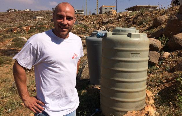 Kasper fra Læger uden Grænser står foran en vandpost i en af de uofficielle teltlejre i Libanon tæt på Syrien