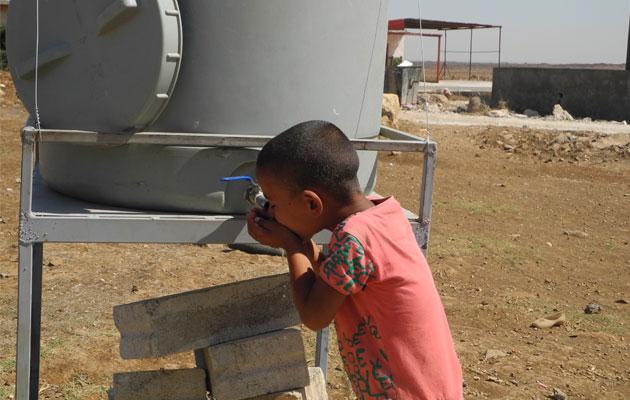 En dreng får sig en tår rent drikkevand fra en af de vandposter, som Læger uden Grænser har installeret.