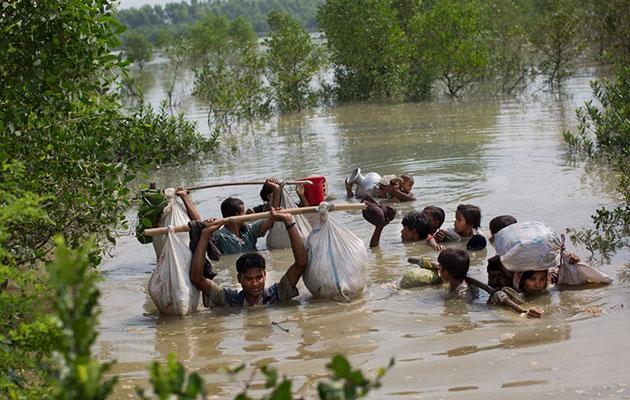 En rohingya-familie krydser en flod for at nå grænsen til Bangladesh.