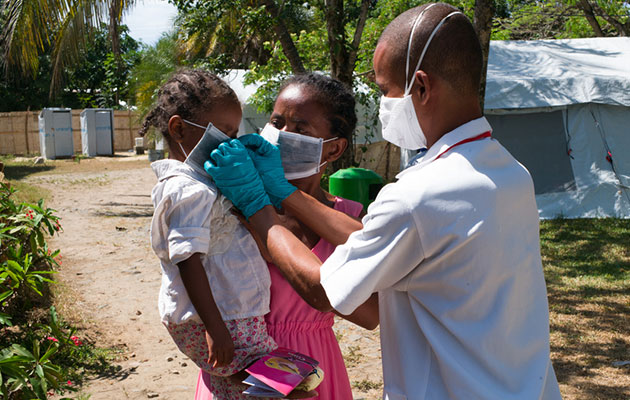 En lille pige får hjælp af en læge på vores pestbehandlingscenter