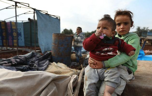 Disse syriske børn er nogle af de mange tusinde nye internt fordrevne. De har kun det tøj de står i, da de er flygtet over hals og hoved. De bor nu under primitive forhold uden adgang til rent drikkevand. Det de har adgang til befinder sig i den rustne tønde i baggrunden. © Omar Haj Kadour/Læger uden Grænser