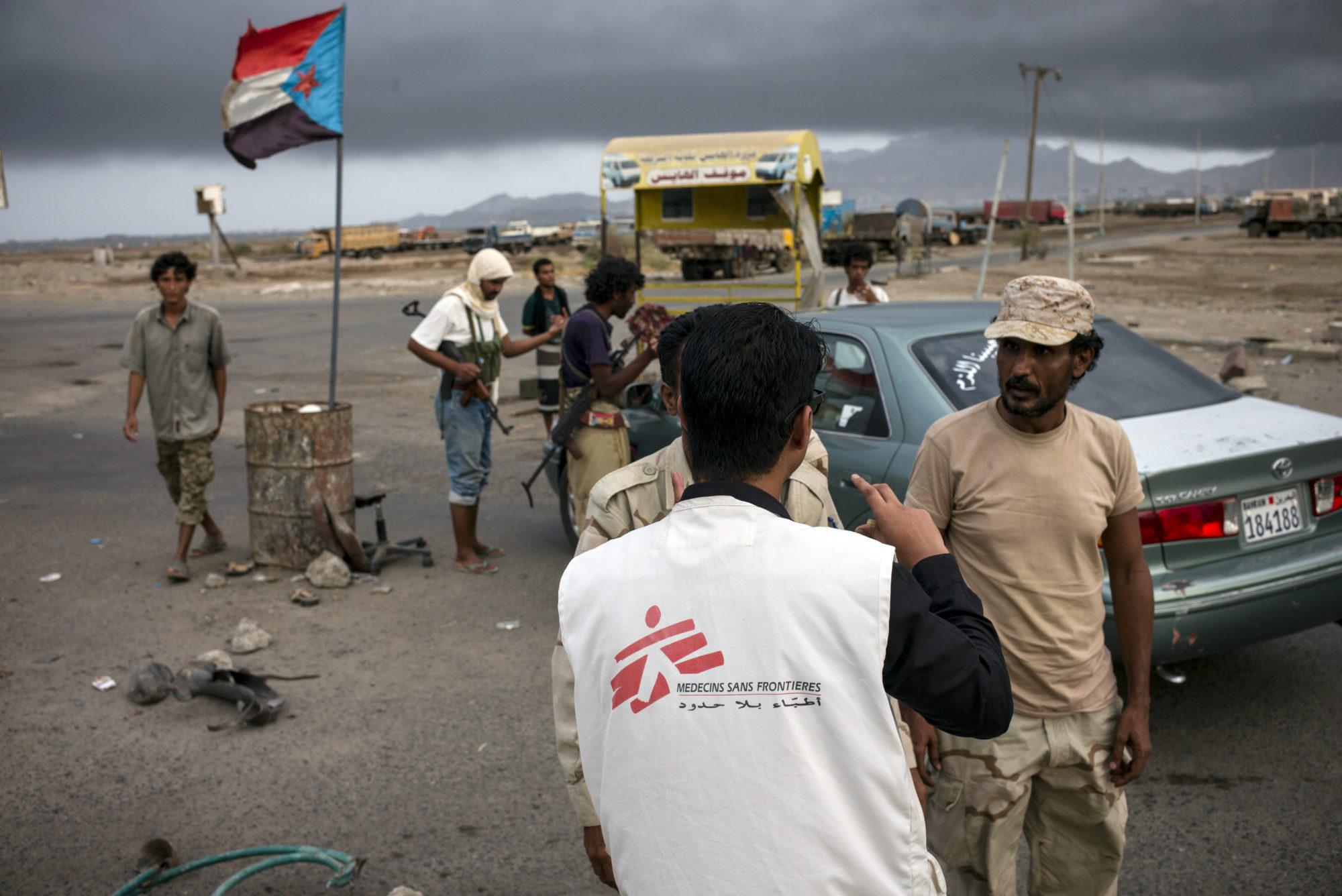 En medarbejder fra Læger uden Grænser taler med væbnede mænd på et checkpunkt i Aden, Yemen.